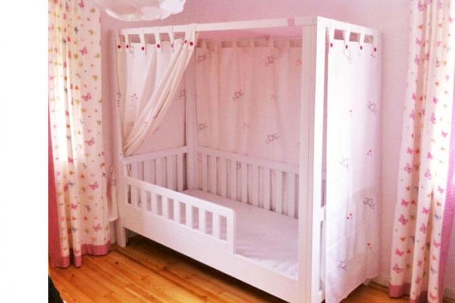 Mädchenzimmer mit weiß lackiertem Himmelbett und rosa Vorhängen